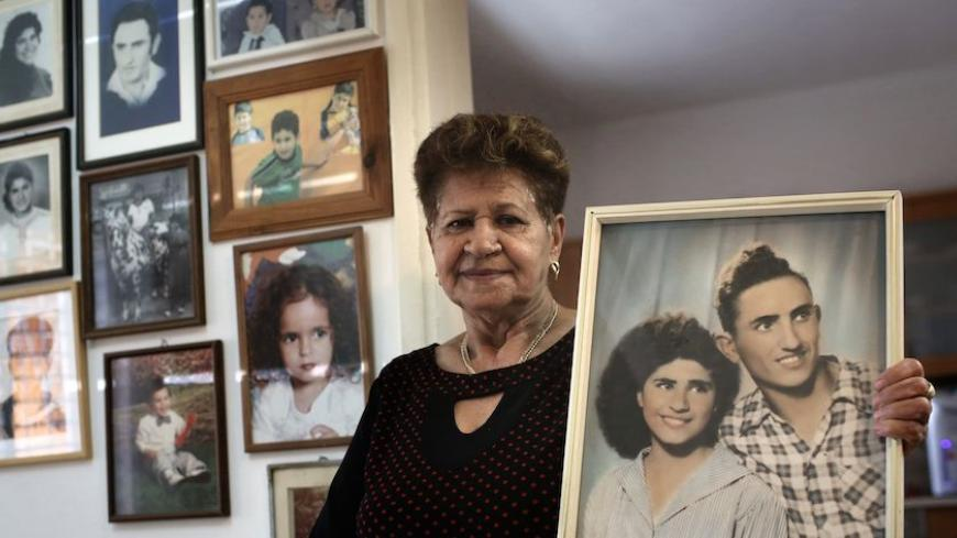 Yona Musa, 76, from a Yemeni descent, poses with a portrait of her and her husband on June 29, 2016 at her home in the Israeli city of Herzliya, near Tel Aviv.  Musa is one of the thousands of Israelis, mainly from Jewish Yemenite families, who claim their babies were abducted more than 60 years ago and handed to adoption. Such stories of babies from immigrant families disappearing have been told in Israel for decades, but growing calls to unseal official documents on the allegations mean new light could so
