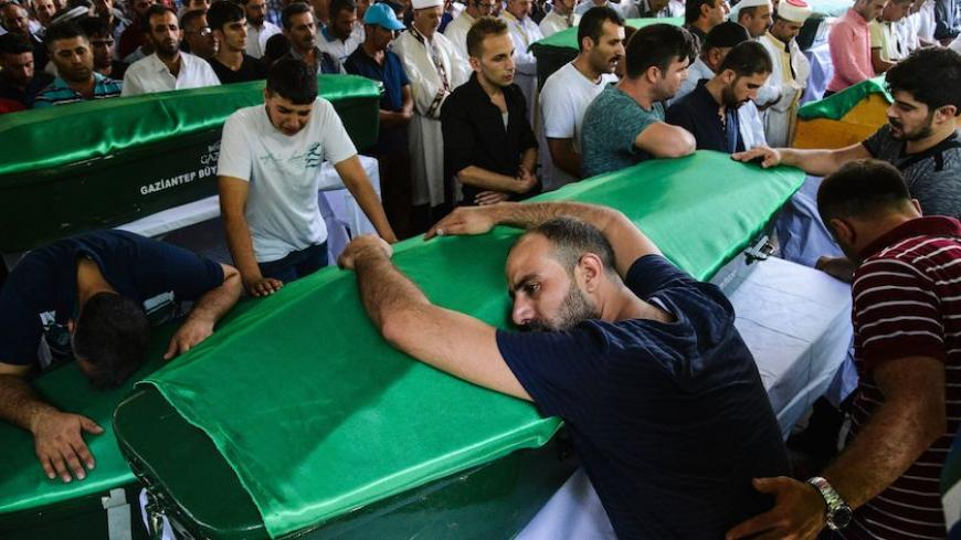 "A man bends on a coffin as people mourn during a funeral for victims of last night's attack on a wedding party that left 50 dead in Gaziantep in southeastern Turkey near the Syrian border on August 21, 2016. At least 50 people were killed when a suspected suicide bomber linked to Islamic State jihadists attacked a wedding thronged with guests, officials said on August 21. Turkish President Recep Tayyip Erdogan said the IS extremist group was the ""likely perpetrator"" of the bomb attack, the deadliest in 2016"