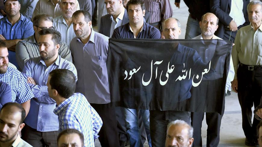 "A man holds a banner that reads ""God's curse on Al Saud (Saudi royal family)"" during the funeral of victims killed in Saudi Arabia in a stampede at the haj pilgrimage, in Tehran October 4, 2015. More than 464 Iranian nationals were killed in last month's crush in Mina, Saudi Arabia, Iran's Haj Organization says. Iranian officials have alleged the overall total death toll is more than 1,000. Saudi Arabia has confirmed the deaths of 769 people. REUTERS/Raheb Homavandi/TIMAATTENTION EDITORS - THIS PICTURE WAS"