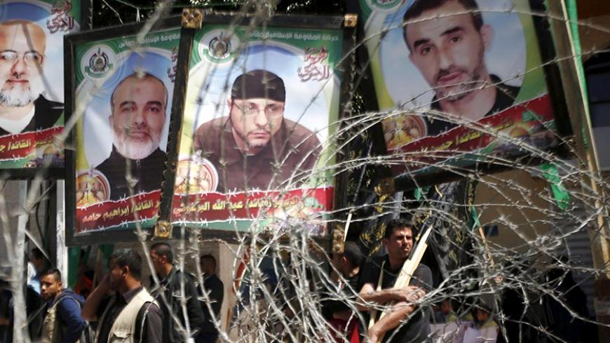 Pictures of Palestinian Hamas militants held in Israeli jails are seen through a fence during a rally marking Palestinian Prisoner Day, in Gaza City April 17, 2016. REUTERS/Mohammed Salem - RTX2AAQR