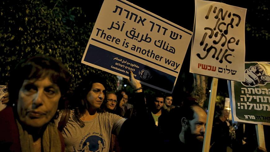 "Israeli left wing demonstrators march holding placards protesting the right wing incitement against President Reuven Rivlin and human rights activists in Tel Aviv. December 19, 2015. An ultra-nationalist Israeli group has published a video accusing the heads of four of Israel's leading human rights organisations of being foreign agents funded by Europe and supporting Palestinians ""involved in terrorism"". The sign (C) reads, ""The right will not silence me."" REUTERS/Baz Ratner - RTX1ZETU"