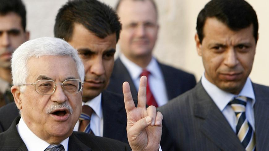 Palestinian President Mahmoud Abbas (L) gestures as Fatah strongman and lawmaker Mohammed Dahlan looks on (R) after meeting with British Prime Minister Tony Blair at the Palestinian Authority headquarters in the West Bank city of Ramallah December 18, 2006. Abbas told Blair on Monday he would push on with plans for early elections despite bitter opposition from the Hamas government. Blair said it was critical that the international community supported the moderate Abbas in the coming weeks. REUTERS/Eliana A
