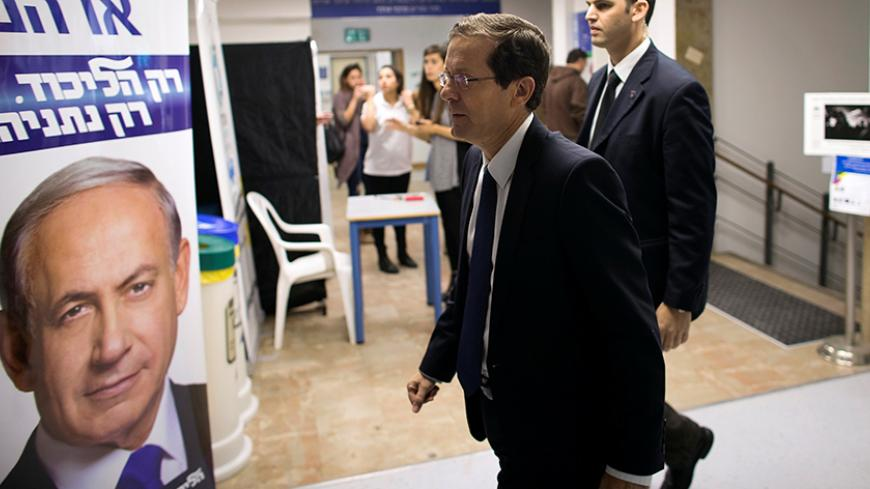 Isaac Herzog (C), co-leader of the Zionist Union party, walks past a Likud party campaign poster, that depicts Israeli Prime Minister Benjamin Netanyahu, as he arrives to address college students in Jerusalem March 10, 2015. REUTERS/Ronen Zvulun/File Photo - RTSEUAJ