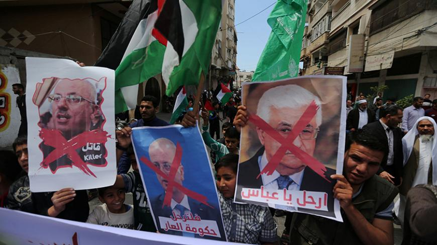 Hamas supporters hold crossed posters depicting Palestinian President Mahmoud Abbas and Palestinian Prime Minister Rami Hamdallah during a protest against them in Khan Younis in the southern Gaza Strip April 14, 2017. REUTERS/Ibraheem Abu Mustafa - RTX35JYQ