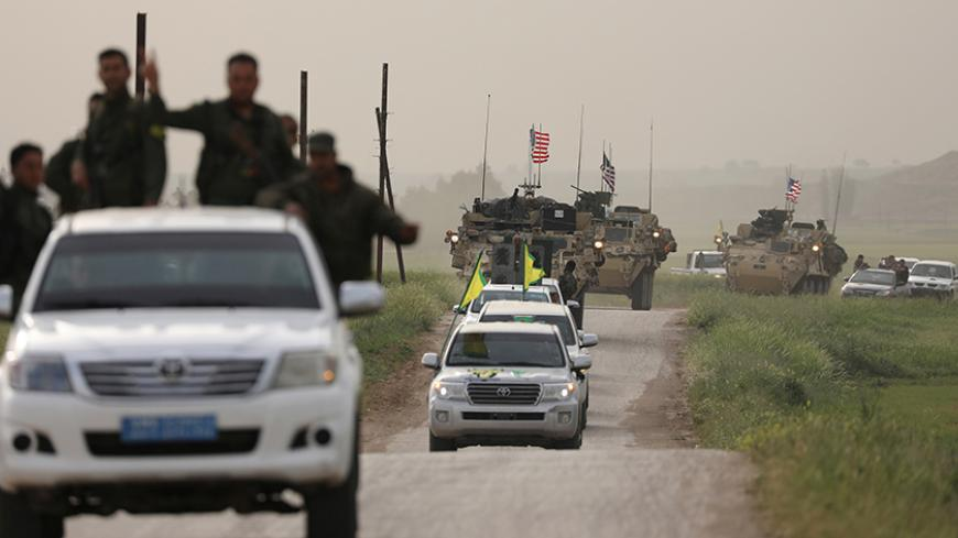 Kurdish fighters from the People's Protection Units (YPG) head a convoy of U.S military vehicles in the town of Darbasiya next to the Turkish border, Syria April 28, 2017. REUTERS/Rodi Said - RTS14EFX