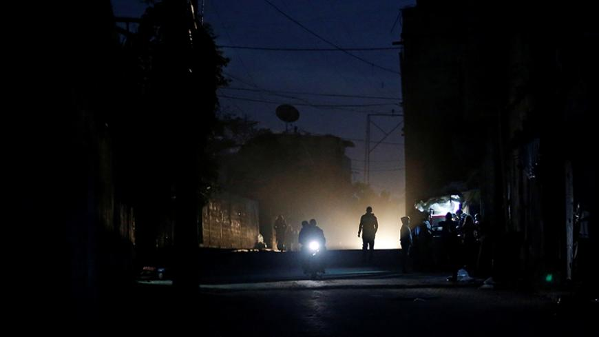 Palestinians ride a motorcycle during a power cut on a street in Beit Lahiya in the northern Gaza Strip January 11, 2017. Picture taken January 11, 2017. REUTERS/Mohammed Salem - RTX2YLZ2