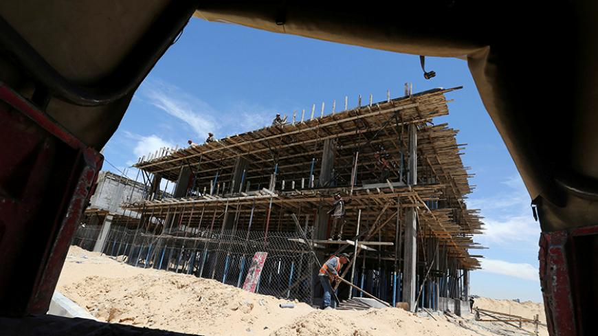 Palestinian workers work on a Qatari-funded construction project in the southern Gaza Strip June 7, 2017. REUTERS/Ibraheem Abu Mustafa - RTX39GD0