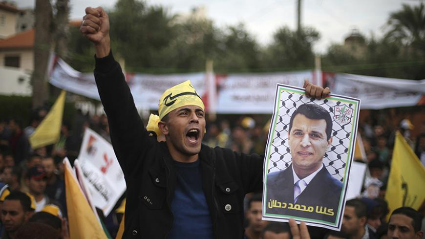 A Palestinian supporter of former head of Fatah in Gaza, Mohammed Dahlan, holds a poster depicting Dahlan during a protest against Palestinian President Mahmoud Abbas in Gaza City December 18, 2014. Dahlan, who lives in exile in the Gulf, is a powerful political foe of Abbas.  REUTERS/Mohammed Salem (GAZA - Tags: POLITICS) - RTR4IJ7B