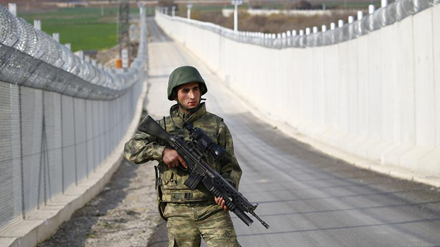 A Turkish soldier patrols along a wall on the border line between Turkey and Syria near the southeastern city of Kilis, Turkey, March 2, 2017. REUTERS/Murad Sezer - RTS114TG