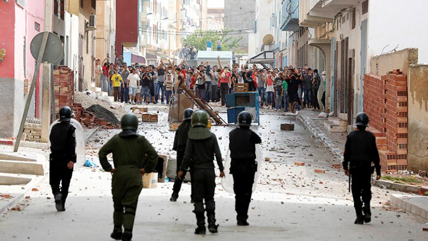 Protesters throw stones towards riot police during a demonstrating against alleged corruption in the provincial town of Imzouren, Morocco, June 2, 2017. REUTERS/Youssef Boudla - RTX38R6V