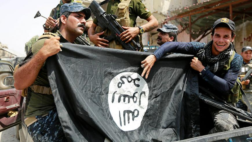 Iraqi Federal Police members hold an Islamic State flag, which they pulled down during fighting between Iraqi forces and Islamic State militants, in the Old City of Mosul, Iraq July 4, 2017. REUTERS/Ahmed Saad - RTX3A0D3
