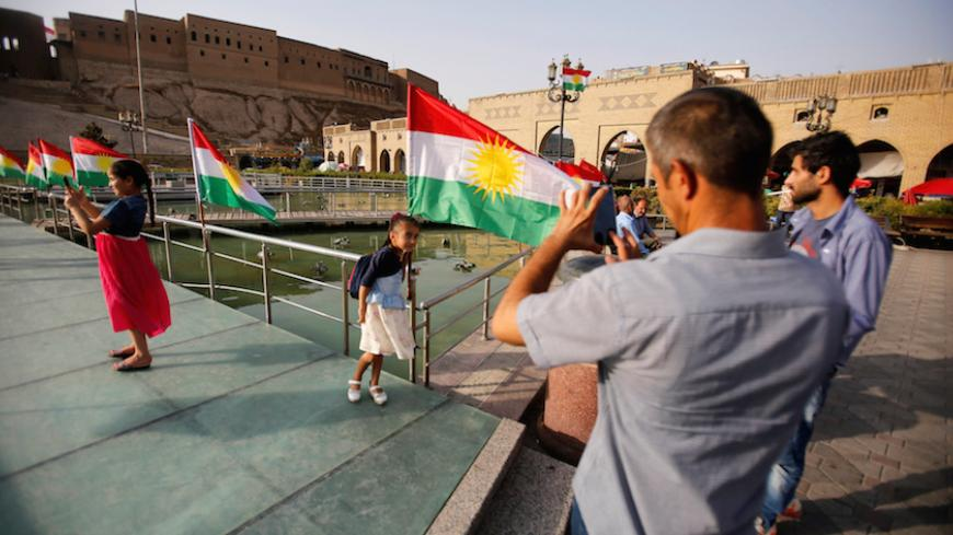 A man takes a picture of his daugther near the Kurdistan flag at the castle of Erbil, Iraq, July 29,2017. REUTERS/Khalid Al-Mousily - RTS19OL9