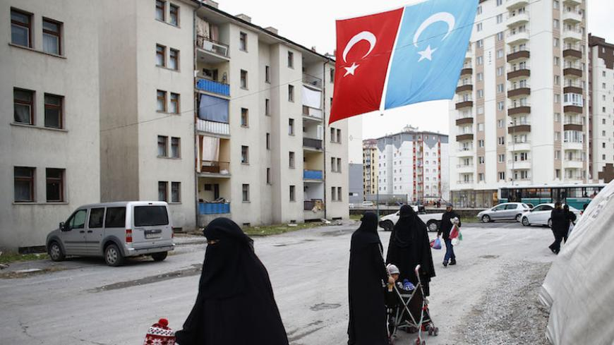 Uighur refugee women walk where they are housed in a gated complex in the central city of Kayseri, Turkey, February 11, 2015. Thousands of members of China's Turkic language-speaking Muslim ethnic minority have reached Turkey, mostly since last year, infuriating Beijing, which accuses Ankara of helping its citizens flee unlawfully. Turkish officials deny playing any direct role in assisting the flight. Picture taken February 11, 2015. To match Insight TURKEY-CHINA/UIGHURS REUTERS/Umit Bektas - RTX1LZ2I