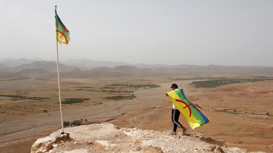 An activist carrying a Berber flag walks on a hilltop above a silver mine, where dozens of poor and unemployed young villagers have been holding a permanent sit-in since 2011, near the town of Imider, southeastern Morocco, August 31, 2015. They have cut off the flow of water from a well that supplies one of the biggest silver mines in Africa. Protesters want to make the company hire more locals and reconsider its water and environmental policies. Picture taken August 31, 2015. REUTERS/Youssef Boudlal - RTX1