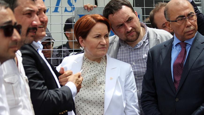 Meral Aksener (C), former interior minister and a lawmaker from Nationalist Movement Party (MHP), stands before the security barriers as police seal off a hotel, preventing dissidents from holding a party congress, in Ankara, Turkey, May 15, 2016. REUTERS/Tumay Berkin/File Photo  - RTX2FHJV