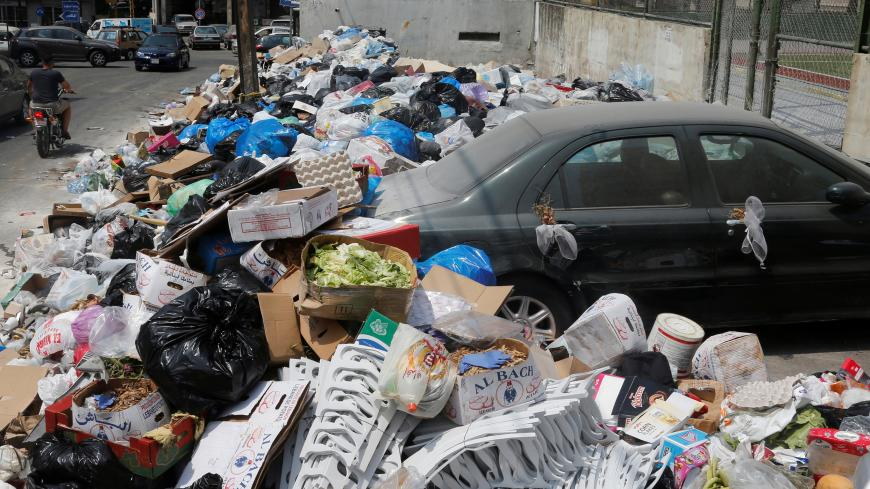 A car is blocked by garbage piled up along a street in Dekwaneh area, Mount Lebanon August 29, 2016. REUTERS/Mohamed Azakir  - S1AETYGHNHAA