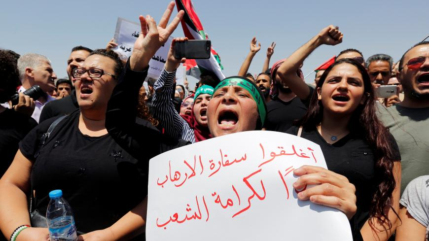 "Protestors chant slogans during a demonstration near the Israeli embassy in Amman, Jordan July 28, 2017. The poster reads ""Close the terrorist embassy, dignity for the people"". REUTERS/Muhammad Hamed - RC1D89B3BBD0"