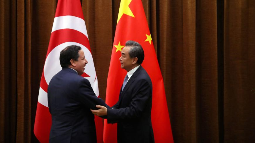 Tunisia's Foreign Minister Khemaies Jhinaoui and Chinese Foreign Minister Wang Yi shake hands as they pose for a photo before a meeting at the Ministry of Foreign Affairs in Beijing, China, July 19, 2017. REUTERS/Mark Schiefelbein/Pool - RC1D72BC9610