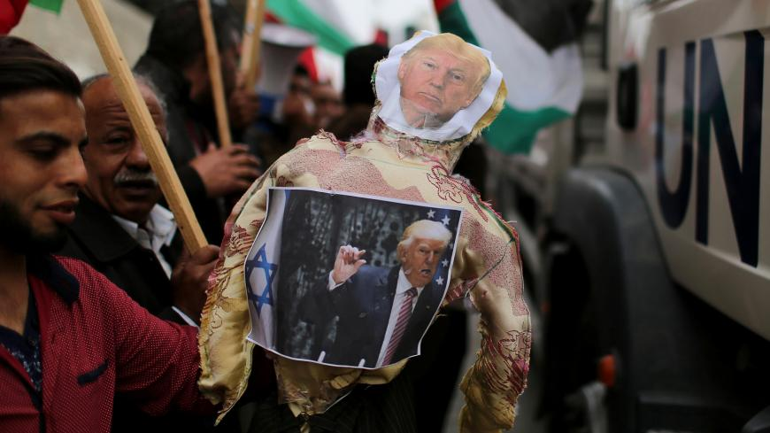 Palestinian demonstrators hold an effigy depicting U.S. President Donald Trump to be burnt during a protest against U.S aid cuts, outside the United Nations' offices in the southern Gaza Strip February 11, 2018. REUTERS/Ibraheem Abu Mustafa - RC19E00C32E0
