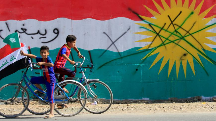 A boy drives a bicycle with an Iraqi flag in Dibis area on the outskirts of Kirkuk, Iraq October 17, 2017. REUTERS/Alaa Al-Marjani - RC1DD9EF0F10