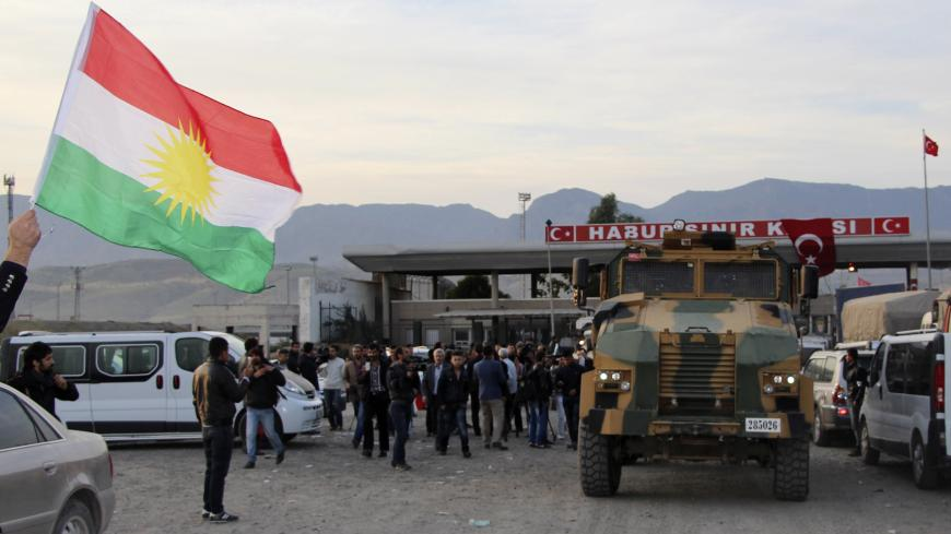A man waves a Kurdistan flag as a Turkish military truck escorts a convoy of peshmerga vehicles at Habur border gate, which separates Turkey from Iraq, near the town of Silopi in southeastern Turkey, October 29, 2014. Iraqi peshmerga fighters arrived in southeastern Turkey early on Wednesday ahead of their planned deployment to the Syrian town of Kobani to help fellow Kurds repel an Islamic State advance, a Reuters witness said. REUTERS/Kadir Baris (TURKEY - Tags: POLITICS MILITARY CONFLICT TPX IMAGES OF TH
