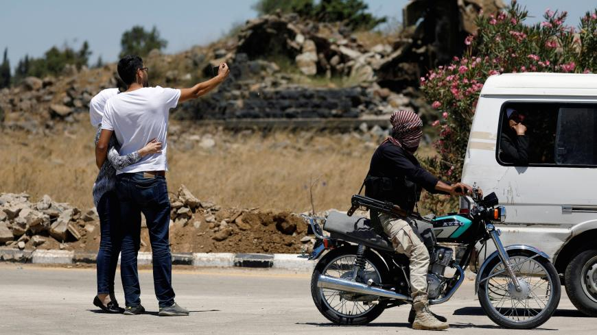 A rebel fighter rides on a motorbike as people take a selfie on a road in Quneitra, Syria July 27, 2018. REUTERS/Omar Sanadiki - RC1305C71BB0