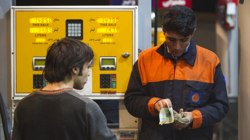 EDITORS' NOTE: Reuters and other foreign media are subject to Iranian restrictions on their ability to film or take pictures in Tehran.   A petrol station attendant (R) counts money as a man waits for his change at a petrol station in northwestern Tehran December 19, 2010. The price of gasoline will rise four-fold in Iran in the coming days, state television announced late on Saturday, as the most politically sensitive part of President Mahmoud Ahmadinejad's subsidy cuts plan takes effect.  REUTERS/Morteza