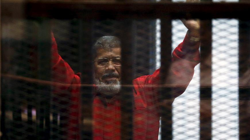 Deposed President Mohamed Mursi greets his lawyers and people from behind bars at a court wearing the red uniform of a prisoner sentenced to death, during his court appearance with Muslim Brotherhood members on the outskirts of Cairo, Egypt, June 21, 2015. REUTERS/Amr Abdallah Dalsh/File Photo - S1AETCRHIPAB