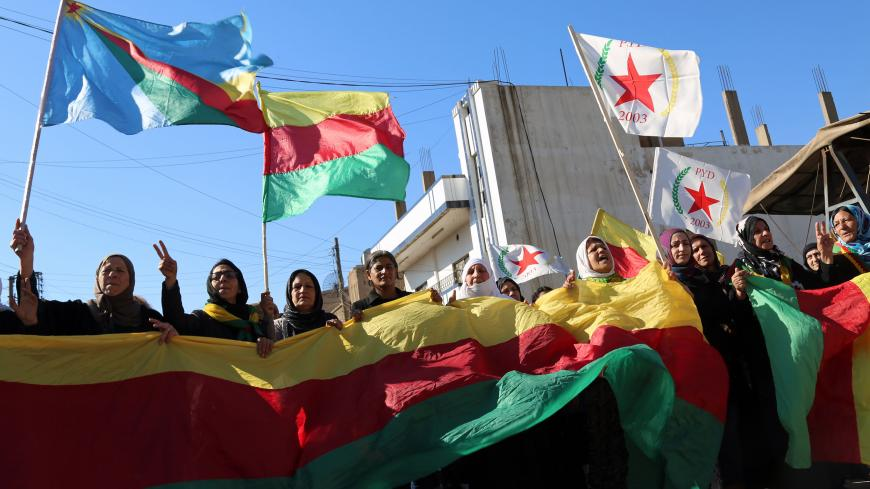 Kurdish women hold flags of the Kurdish People's Protection Units (YPG) political wing, the Democratic Union Party (PYD), and banners during a demonstration against the exclusion of Syrian-Kurds from the Geneva talks in the northeastern Syrian city of Qamishli on February 4, 2016.   The talks in Geneva are the latest bid to end Syria's conflict, nearly five years after it began in March 2011 with anti-government protests. But they have stalled over the make-up of the opposition as well as its insistence tha