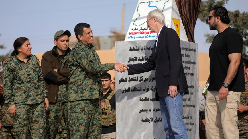 Mazloum Kobani, SDF's commander in chief, shakes hands with the advisor for the US Department of State in northern Syria William Robak, at al-Omar oil field in Deir Al Zor, Syria March 23, 2019. REUTERS/Rodi Said - RC142AE67C90