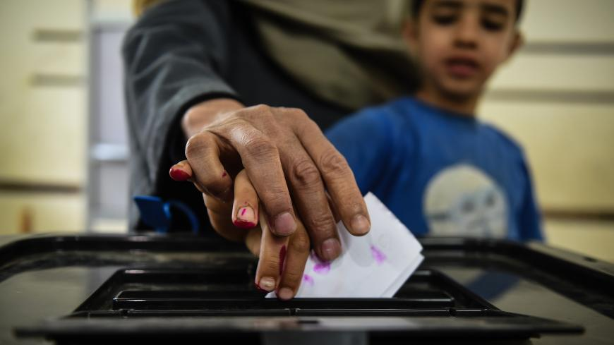 An man Egyptian casts his ballot with a child at a polling station during the third day of a referendum on constitutional amendments, at a school in shamma village in the northern Nile delta province of Menoufia, on April 22, 2019. (Photo by Mohamed el-Shahed / AFP)        (Photo credit should read MOHAMED EL-SHAHED/AFP/Getty Images)