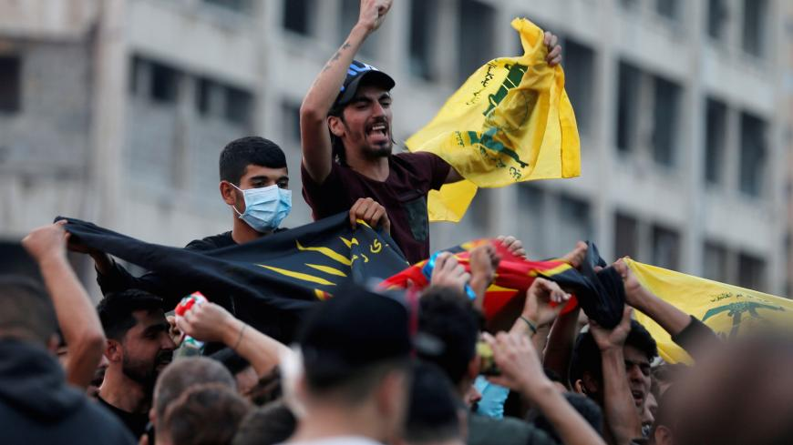 Supporters of Lebanon's Hezbollah leader Sayyed Hassan Nasrallah carry the party's flag in Beirut, Lebanon, October 25, 2019. REUTERS/Mohamed Azakir - RC1916F5C910