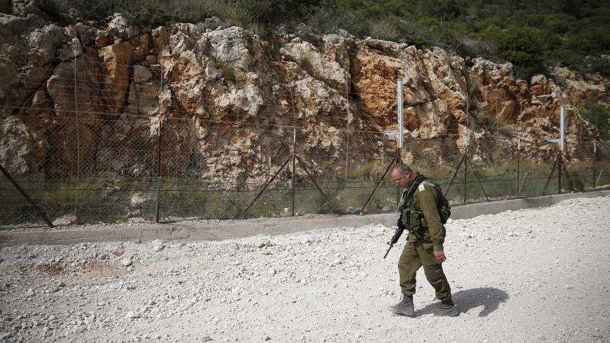 An Israeli soldier walks near the area where the Israeli army is excavating part of a cliff to create an additional barrier along its border with Lebanon, near the community of Shlomi in northern Israel April 6, 2016. Israeli Defence Forces (IDF) Lieutenant-General Eli David, who serves as an engineering officer in a northern division, told Reuters on Wednesday that the army began work on the new barrier by exposing the cliff in January 2015, to help protect communities located close to the Lebanese border