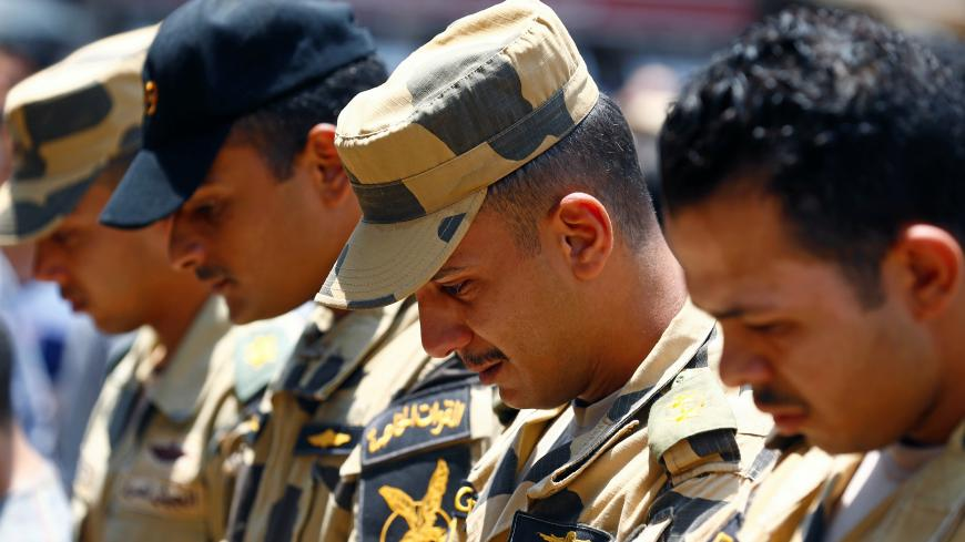 Egyptian army officers react during the funeral of officer Khaled al-Maghrabi, who was killed during a suicide bomb attack on an army checkpoint in Sinai, in his hometown Toukh, Al Qalyubia Governorate, north of Cairo, Egypt 8 July, 2017. REUTERS/Mohamed Abd El Ghany - RC15CBC45300