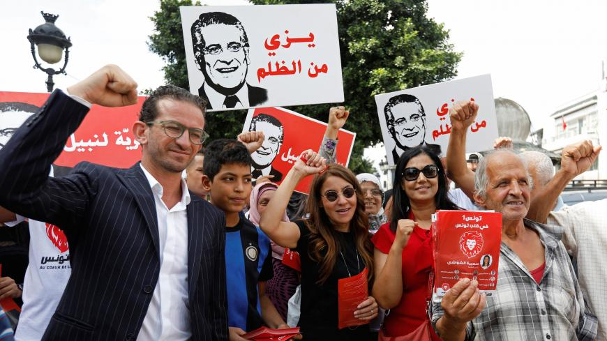 Saloua Samoui, the wife of detained Tunisian media mogul and presidential candidate Nabil Karoui, stands with supporters as she distributes election leaflets for Karoui's Heart of Tunisia party ahead of the upcoming parliamentary elections in Tunis, Tunisia October 3, 2019. Picture taken October 3, 2019. REUTERS/Zoubeir Souissi - RC1A9FEF8FC0