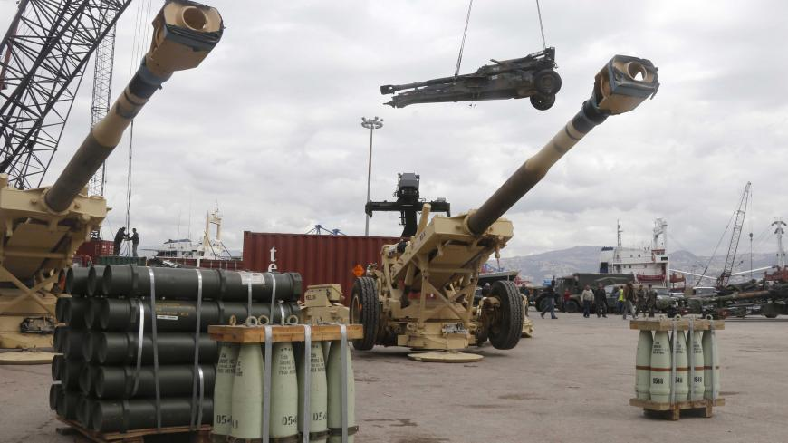Workers unload artillery, part of a military donation from the U.S. government to the Lebanese army, during a ceremony at Beirut's port February 8, 2015. More than 70 M198 Howitzers, as well as 26 million rounds of ammunition including small, medium, and heavy artillery rounds, were delivered on Sunday  from the United States as military aid to the Lebanese army. REUTERS/Mohamed Azakir (LEBANON - Tags: POLITICS MILITARY) - GM1EB281REZ01