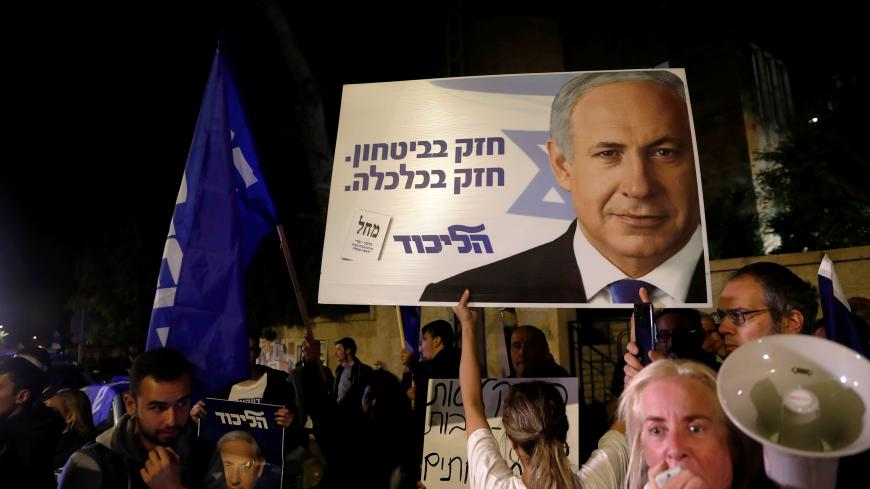 "Supporters of Israeli Prime Minister Benjamin Netanyahu protest outside his residence following Israel's Attorney General Avichai Mandelblit's indictment ruling in Jerusalem November 21, 2019. The placards in Hebrew read, ""Strong in security Strong in Economy "". REUTERS/Ronen Zvulun - RC2UFD9194FK"