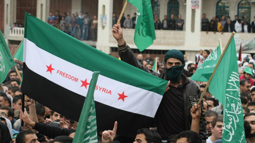 Palestinian supporters of the Islamist movement Hamas wave their flag and a pre-Baath Syrian flag (C) during a demonstration in the West Bank city of Hebron on November 21, 2012, against the ongoing Israeli military offensive on the Gaza Strip. Israel launched its offensive on November 14 with the targeted killing of a Hamas military chief. Since then, 147 Palestinians and five Israelis have been killed. AFP PHOTO/HAZEM BADER        (Photo credit should read HAZEM BADER/AFP via Getty Images)