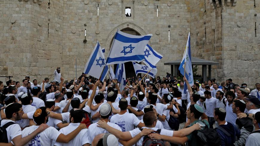 "TOPSHOT - Israeli nationalist settlers wave their national flag as they celebrate the Jerusalem Day at the Old City's Damascus gate in Jerusalem on May 13, 2018. - For Israelis, Sunday is Jerusalem Day, an annual celebration of the ""reunification"" of the city following the 1967 Six-Day War. (Photo by MENAHEM KAHANA / AFP)        (Photo credit should read MENAHEM KAHANA/AFP via Getty Images)"