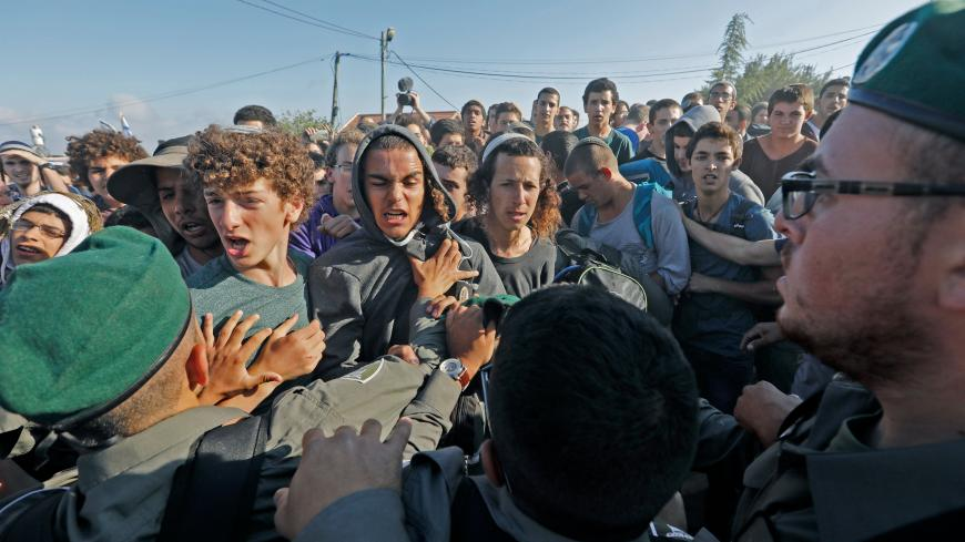 TOPSHOT - Israeli settlers scuffle with Israeli security forces at Netiv Haavot settlement, near Bethlehem, in the occupied West Bank on June 12, 2018. - Fifteen Israeli settler families are expected to evacuate their homes in this outpost after it was declared illegal by the Israeli High Court (Photo by Menahem KAHANA / AFP)        (Photo credit should read MENAHEM KAHANA/AFP via Getty Images)