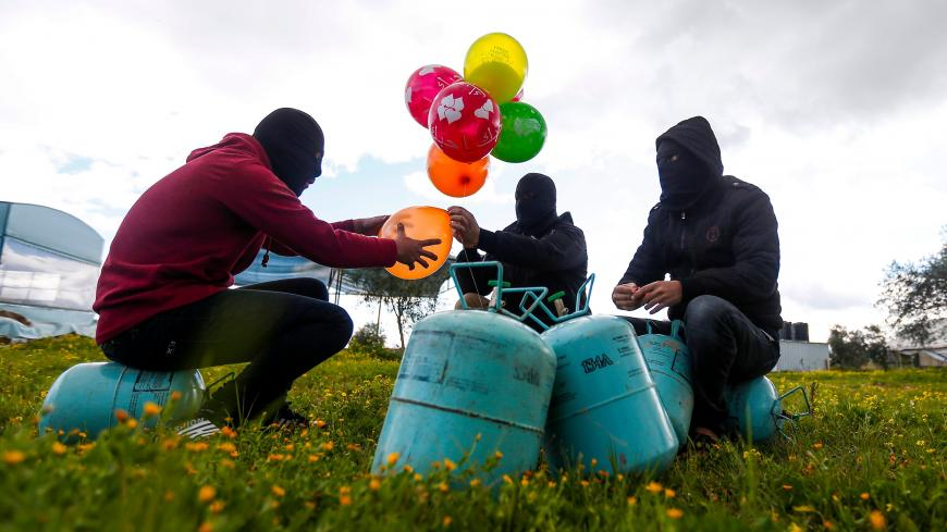 Masked Palestinians prepare to attach balloons to a gas canister before releasing it near Gaza's Bureij refugee camp, along the Israel-Gaza border fence, on February 10, 2020. (Photo by MAHMUD HAMS / AFP) (Photo by MAHMUD HAMS/AFP via Getty Images)
