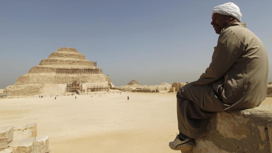 A guide sits on a stone as he looks at the Djoser's step pyramid in Saqqara, outside of Cairo March 5, 2011. Sites around the great pyramid at Giza, a Wonder of the Ancient World, the Sphinx and the cemetery at Sakkara have been nearly empty of tourists since a revolt started a month ago that ousted Hosni Mubarak and now Egypt wants visitors to return. REUTERS/Peter Andrews (EGYPT - Tags: CIVIL UNREST POLITICS TRAVEL SOCIETY) - GM1E7351JOK01