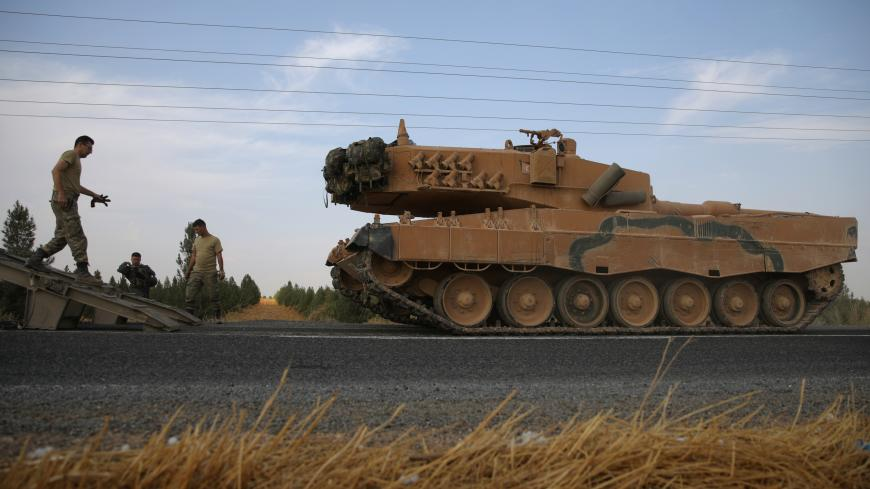 Turkish army tank is being unloaded on a road near the Turkish border town of Ceylanpinar, Sanliurfa province, Turkey, October 18, 2019. REUTERS/Stoyan Nenov - RC1C41D0BF40