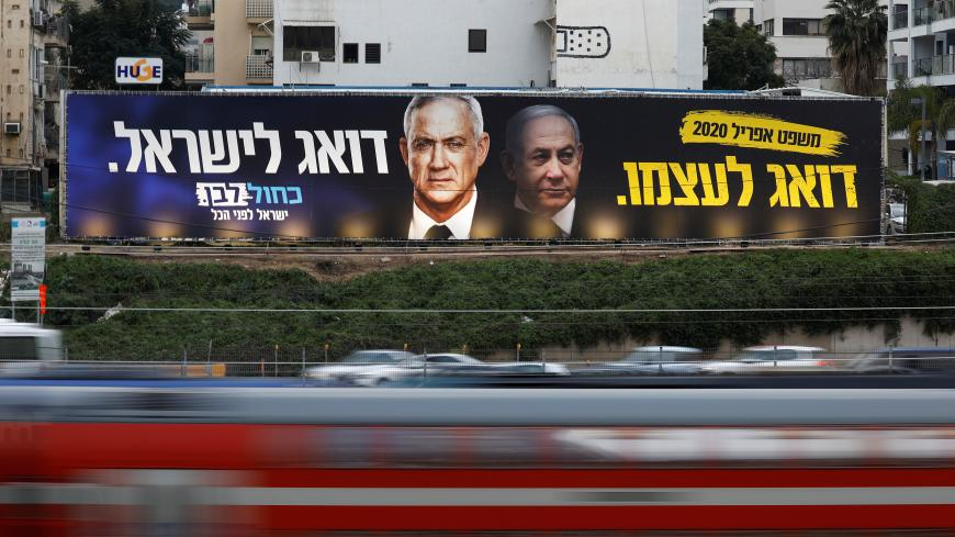 Traffic moves past a Blue and White party election campaign poster, depicting party leader Benny Gantz, and Israeli Prime Minister Benjamin Netanyahu, in Tel Aviv, Israel February 18, 2020. REUTERS/Amir Cohen - RC243F9KEJJJ