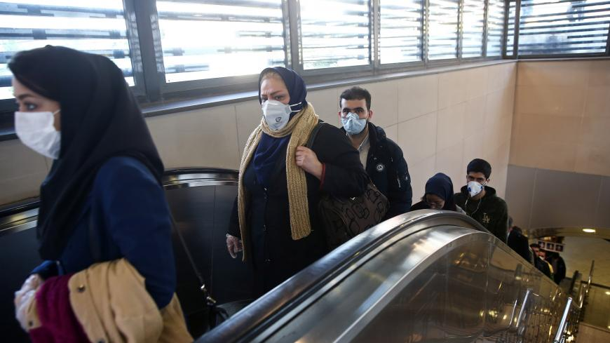 Iranian people wear protective masks to prevent contracting a coronavirus, as they climb an escalator in Tehran, Iran February 29, 2020. WANA (West Asia News Agency)/Nazanin Tabatabaee via REUTERS ATTENTION EDITORS - THIS PICTURE WAS PROVIDED BY A THIRD PARTY - RC2BAF97VRQP