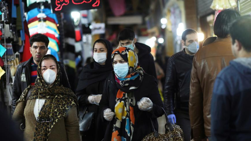 People wear protective face masks and gloves, amid fear of coronavirus disease (COVID-19), as they walk at Tajrish market, ahead of the Iranian New Year Nowruz, March 20, in Tehran, Iran March 18, 2020. Picture taken March 18, 2020. WANA (West Asia News Agency)/Ali Khara via REUTERS ATTENTION EDITORS - THIS PICTURE WAS PROVIDED BY A THIRD PARTY - RC22NF92HAWR