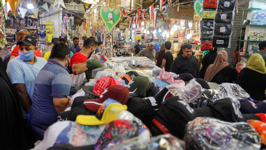 People shop after the lockdown measures, following the outbreak of the coronavirus disease (COVID-19), were partially eased, to prepare for the holy month of Ramadan, in Baghdad, Iraq, April 21, 2020. REUTERS/Khalid al Mousily - RC2Y8G9E0PGC