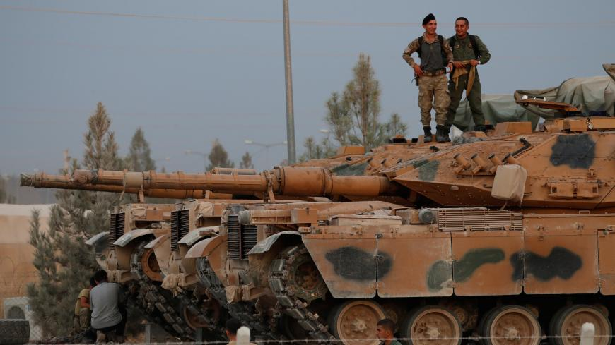 Turkish soldiers stand on top of a tank in the border town of Akcakale in Sanliurfa province, Turkey, October 11, 2019. REUTERS/Murad Sezer - RC146E7AC710