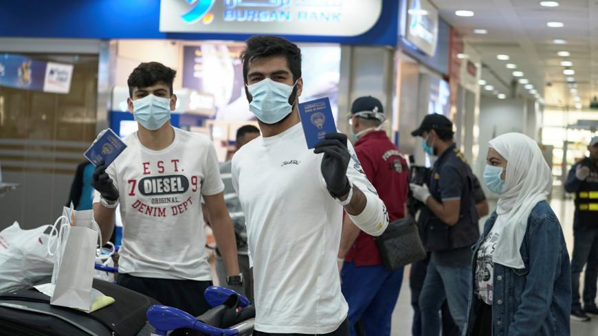 Kuwaiti boys wearing protective face masks and quarantine tracking bracelets, following the outbreak of the coronavirus disease (COVID-19), pose for the camera as they hold up their passports upon arrival from Amman, to Kuwait Airport in Kuwait, Kuwait April 21, 2020. REUTERS/Stephanie McGehee - RC229G91CPDO