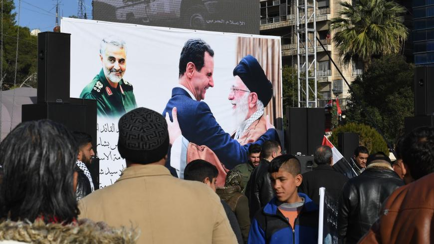 Syrian demonstrators look at a poster bearing the portraits of Iran's Supreme Leader Ayatollah Ali Khamenei (C-R) and Syrian President Bashar al-Assad (C) in the central Saadallah al-Jabiri square in the northern Syrian city of Aleppo on January 7, 2020, to mourn and condemn the death of Iranian military commander Qasem Soleimani (portrait-L), and nine others in a US air strike in Baghdad. (Photo by - / AFP) (Photo by -/AFP via Getty Images)